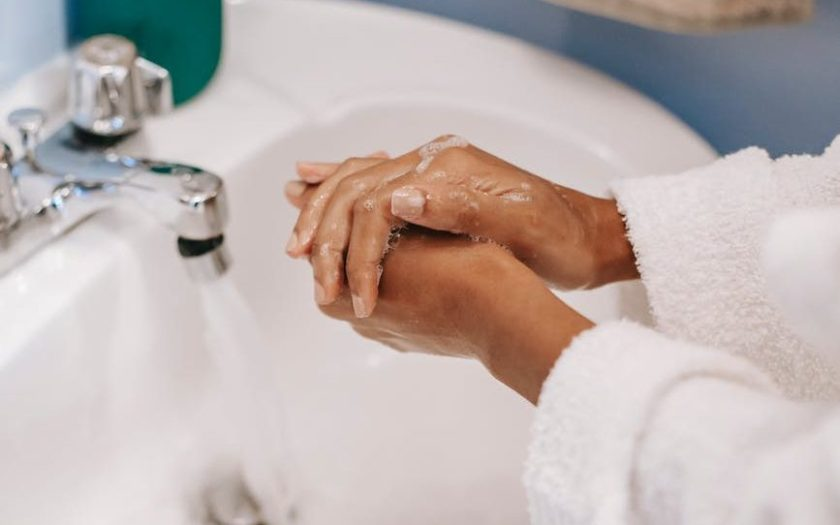 black woman washing hands with soap