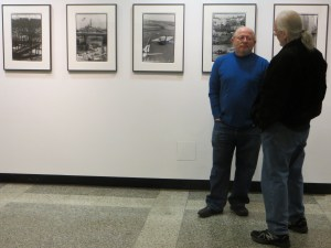 David Akiba and a guest to the exhibit with Akiba's photographies in the background