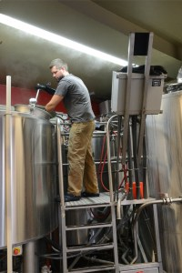 Brewer Greg Doroski mixes the grain by hand using a giant metal oar. Photo by Alex Goetzfried