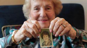 Fleischmann holding a photo of herself at age 38.