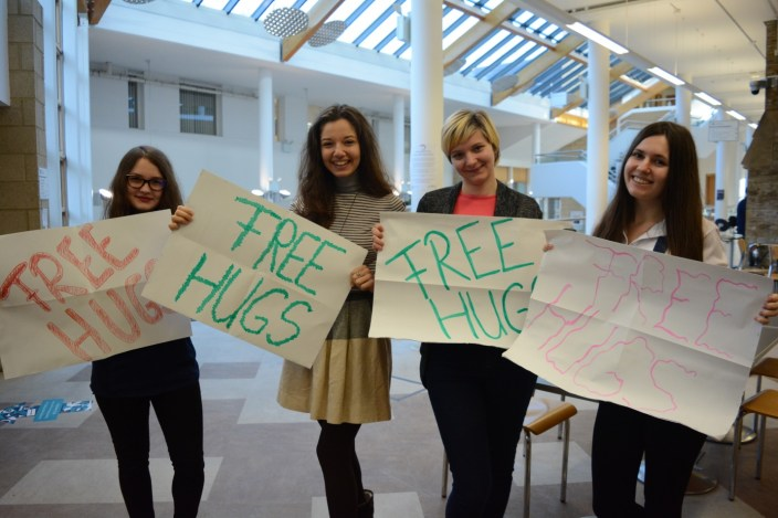Bianca and other volunteers with Free Hugs signs