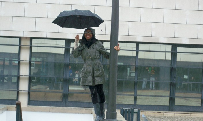 Toyin with umbrella on lamppost.