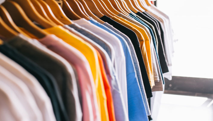 Rail of different coloured t-shirts in a store