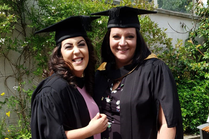 Emma and her friend posing for a photo at her graduation.