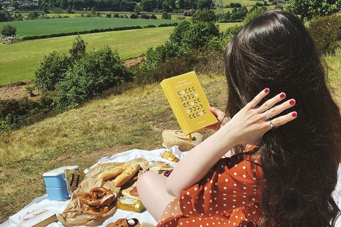 A person having a picnic and reading a book in the countryside.