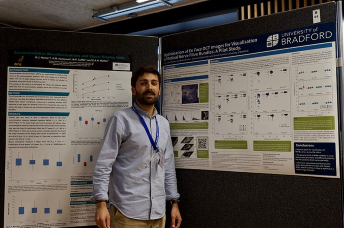 Riccardo stood in front of two boards displaying his research findings.