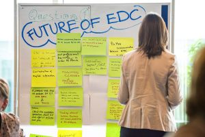 A woman with her back to the camera is looking at a whiteboard covered in sticky notes.