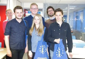 Five men and a woman are smiling at the camera. Two of them are holding Europe Direct bags.