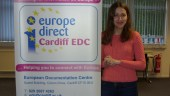 A woman with long hair is smiling at the camera. She is stands next to a banner with 'europe direct Cardiff EDC' written on it.