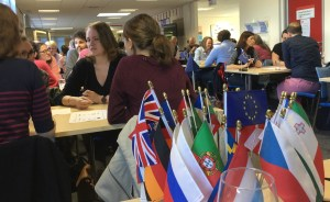 People sitting at tables, with European flags in the foregraound.