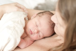 Newborn baby boy sleeping at mums chest