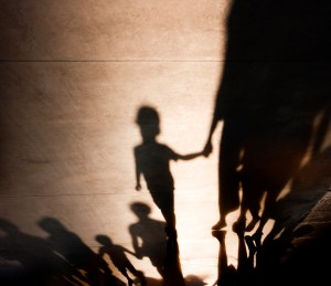 Blurry shadows silhouettes of families with kids  walking and holding hands on misty summer promenade