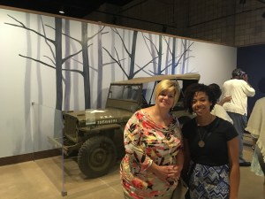two people in the foreground, jeep in the background and in the far background there is a trees mural painted on wall