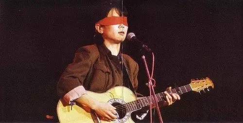 Jian Cui was singing with a piece of red cloth covering his eyes.