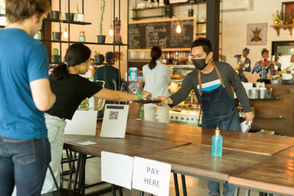 Social distancesmall business waiter serving customer in cafe