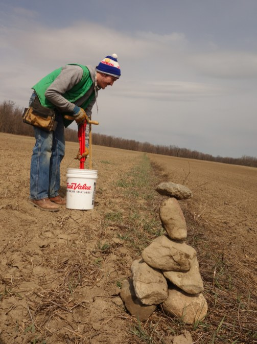 "Chris Pelzer samples soil near a homemade ""flag"", for dividing up the field for even sampling"