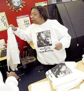 Ida Johnson helps with shirt sales at United Neighbors Inc. in Davenport on Martin Luther King Day.