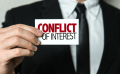 "image of hand holding card with words ""conflict of interest"""