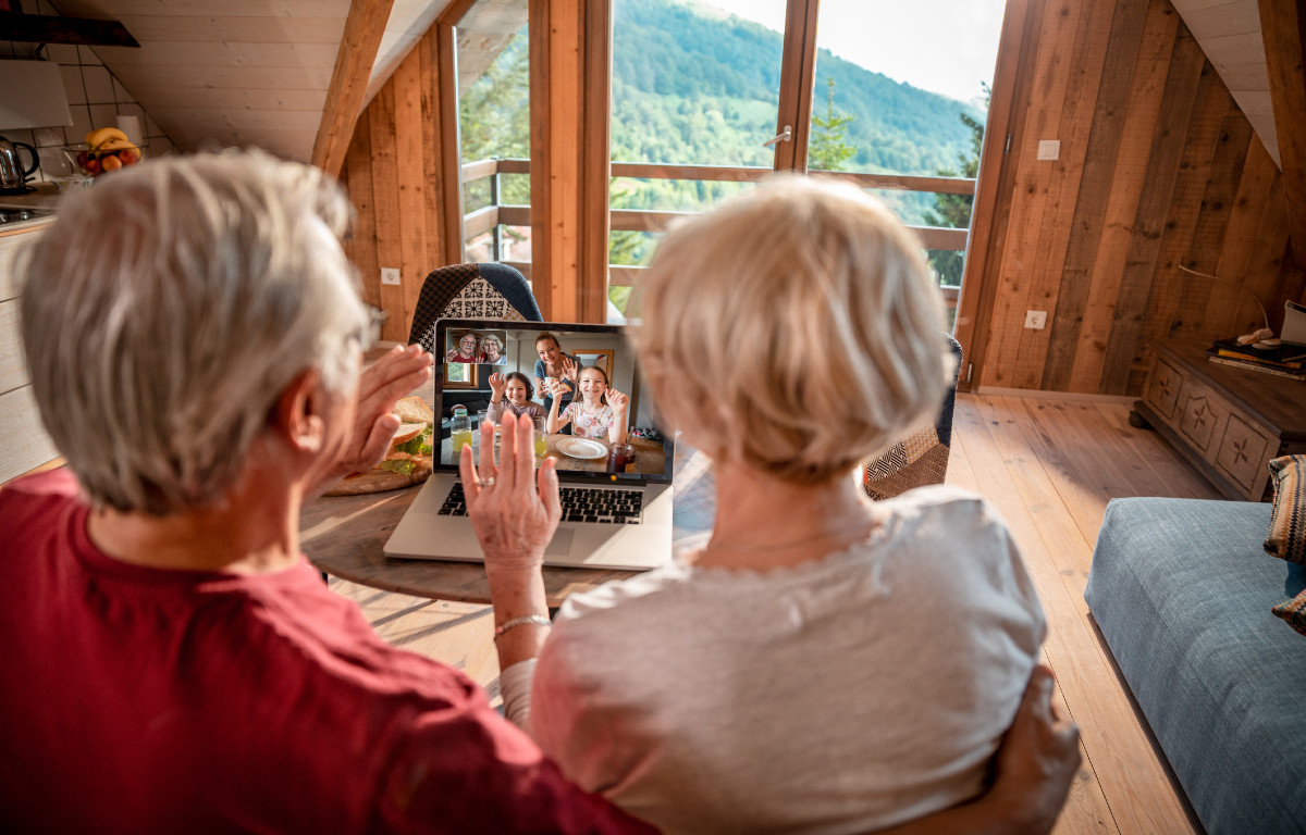Back of heads of older couple looking at laptop with images of family waving back at them