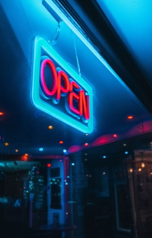 front view of a shop at night with open written on a banner