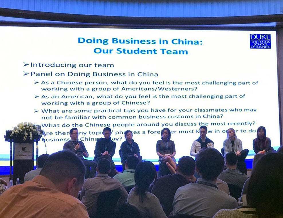 seven student seated on stage with a PowerPoint about doing business in China running behind them; key learnings