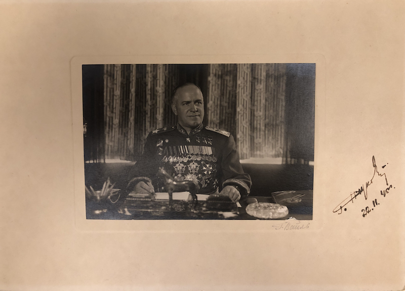 A black-and-white portrait of Marshal Zhukov sitting behind his desk wearing his dress uniform and medals.