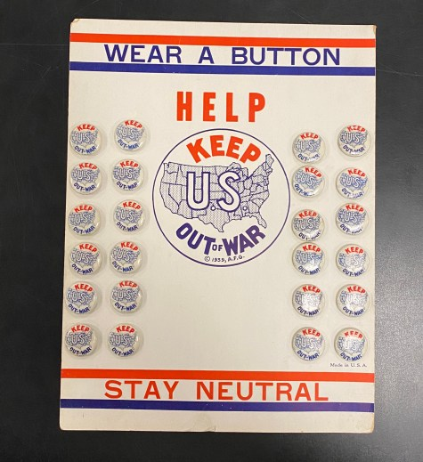 "A cardboard card holds 24 lapel buttons. The card and each button have a US map with the words ""Keep U.S. Out of War"" and the card advises to ""Wear a Button"" and ""Stay Neutral."""