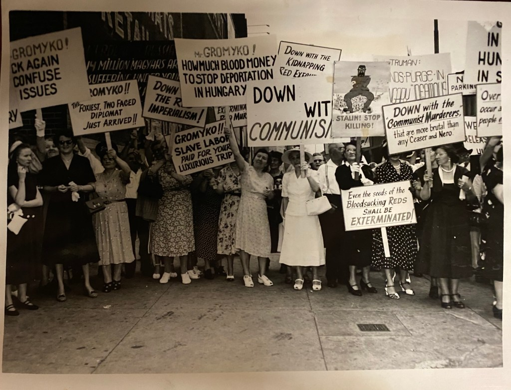 A group of sign-carrying protestors, mostly women, march against communism.