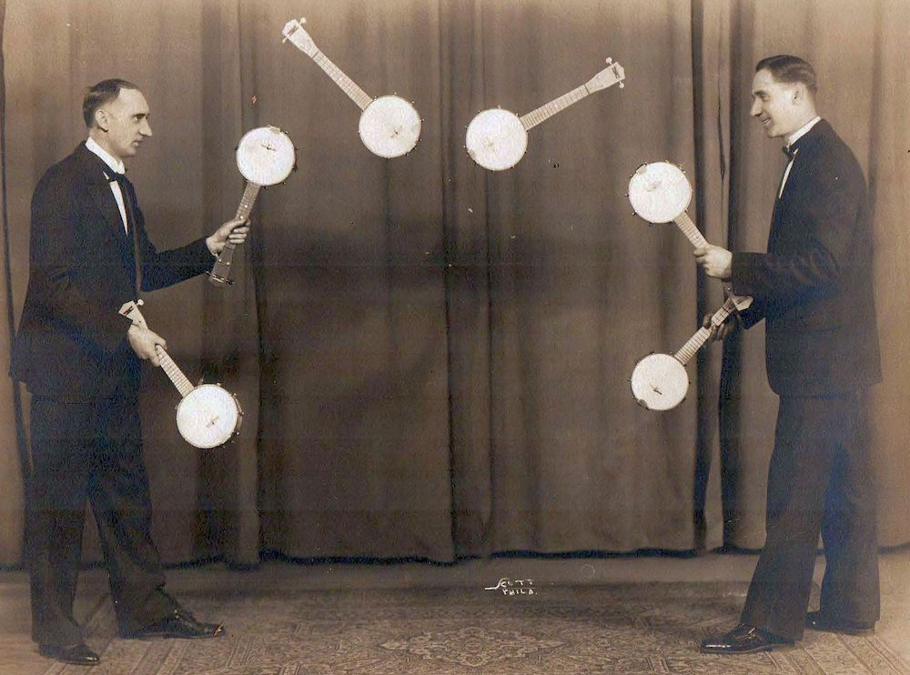 A photograph of two men juggling 6 banjos between them.