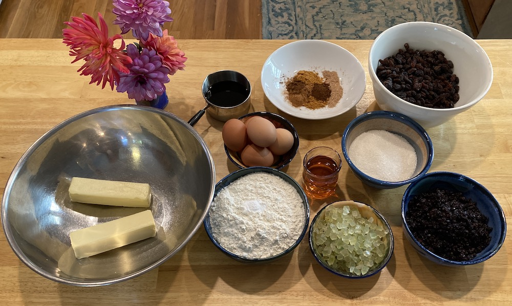 Ingredients for a quarter recipe of Emily Dickinson's Black Cake: butter, molasses, flour, eggs, spices, brandy, sugar, and dried fruit.