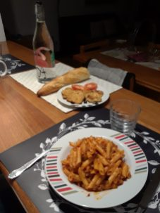 Pasta, breaded chicken, tomatoes, and bread