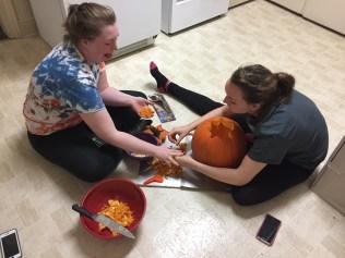 two girls emptying pumpkin guts