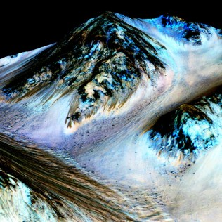 These dark, narrow 100-meter-long streaks called recurring slope lineae flowing downhill on Mars are inferred to have been formed by contemporary flowing water. Recently, planetary scientists detected hydrated salts on these slopes at Hale crater, corroborating their original hypothesis that the streaks are indeed formed by liquid water. The blue color seen upslope of the dark streaks are thought not to be related to their formation, but instead are from the presence of the mineral pyroxene. The image is produced by draping an orthorectified (Infrared-Red-Blue/Green(IRB)) false color image (ESP_030570_1440) on a Digital Terrain Model (DTM) of the same site produced by High Resolution Imaging Science Experiment (University of Arizona). Vertical exaggeration is 1.5. Credits: NASA/JPL/University of Arizona