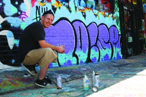 """Dillion Herd (JCCC student and Graffiti artist) shows his finished project. Herd domonstrated the process on Saturday, Sept. 26, 2015 at """"Legal Alley"""" downtown Kansas City."""