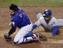 New York Mets catcher Travis d'Arnaud was pulled off home plate by a wide throw, so he missed a chance to tag Kansas City Royals first baseman Eric Hosmer, who scored in the ninth inning during Game 5 of the World Series on Sunday, Nov. 1, 2015, at Citi Field in New York. Photo courtesy of Kansas City Star, Jill Toyoshiba jtoyoshiba@kcstar.com