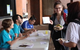 There was a table at the end of the food line where people could attempt to write their names in different languages. Photo by: Jennifer Tharp, The Campus Ledger.