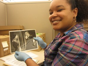 Star Intern, Gabby Womack holding a photograph from the Mildred Freed Alberg collection.
