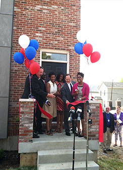 Officials cut the ribbon Aug. 23 to mark the completion of Lutheran Housing Support's first of 20 homes in the Nazareth Homes development in St. Louis' College Hill neighborhood. From left, LCMS President Rev. Dr. Matthew C. Harrison, St. Louis Board of Aldermen President Lewis Reed, St. Louis Alderwoman Dionne Flowers, St. Louis Treasurer Tishaura O. Jones, St. Louis Mayor Francis G. Slay and Nicole Ridley, chief executive officer of LCMS National Housing Support Corp., also known as Lutheran Housing Support. (LCMS Communications)