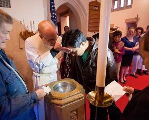 """The Rev. Matthew Clark baptizes Nepali immigrant Rana Tamang at Ascension Lutheran Church. """"It's not always comfortable, but it's a blessing,"""" Clark said about the congregation's work with the Nepalese community. (LCMS Communications/Erik M. Lunsford)"""