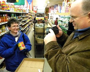 """""""All right. We're ready to go,"""" the Rev. Dale Kaster tells his wife, Suzanne — snapping a photo of her as she holds up a can of GhanaFresh palm nut oil during the missionary-orientation group's Feb. 10 stop at Jay International Food Co. in South St. Louis. The Kasters, of Jacksonville, Fla., are preparing for life in Ghana, where he will serve as a theological educator preparing men for ministry. (LCMS Communications/Joe Isenhower Jr.)"""