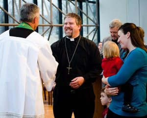 The Rev. Randall Golter, executive director of the LCMS Office of International Mission, congratulates the Rev. Micah and Robin Wildauer during the Rite of Sending for missionaries on Feb. 14, 2014. (LCMS Communications/Erik M. Lunsford)