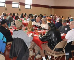 Residents from the neighborhoods around St. Paul Lutheran Church, Cincinnati, enjoy a Christmas dinner in the church's renovated gym. The congregation led by then-Pastor Rev. Steve Schave held the dinner so no one would be alone or in need on Christmas Day. (St. Paul Lutheran Church)