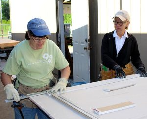 From left, Laborers Kim Heaps of Redding, Calif., and Phyllis Bockelmann, Dow City, Iowa, cut sheet rock as part of the renovation and energy-efficiency project at Trinity Lutheran School, Portland, Ore. The congregation is participating in Lutheran Church Extension Fund's Laborers For Christ to make the improvements. (Lisa Noreen)
