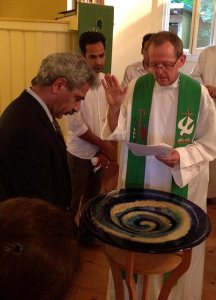 The Rev. Hugo Gevers prays for Eizadi Shahriyar during the German and Farsi Baptismal Rite July 27 at St. Trinitatisgemeinde (Holy Trinity Lutheran Church) in Leipzig. (St. Trinitatisgemeinde)