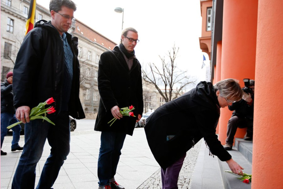 People place flowers for the victims of the Brussels attacks in front of the Belgian Embassy in Berlin on March 22. (Courtesy of REUTERS/Fabrizio Bensch)