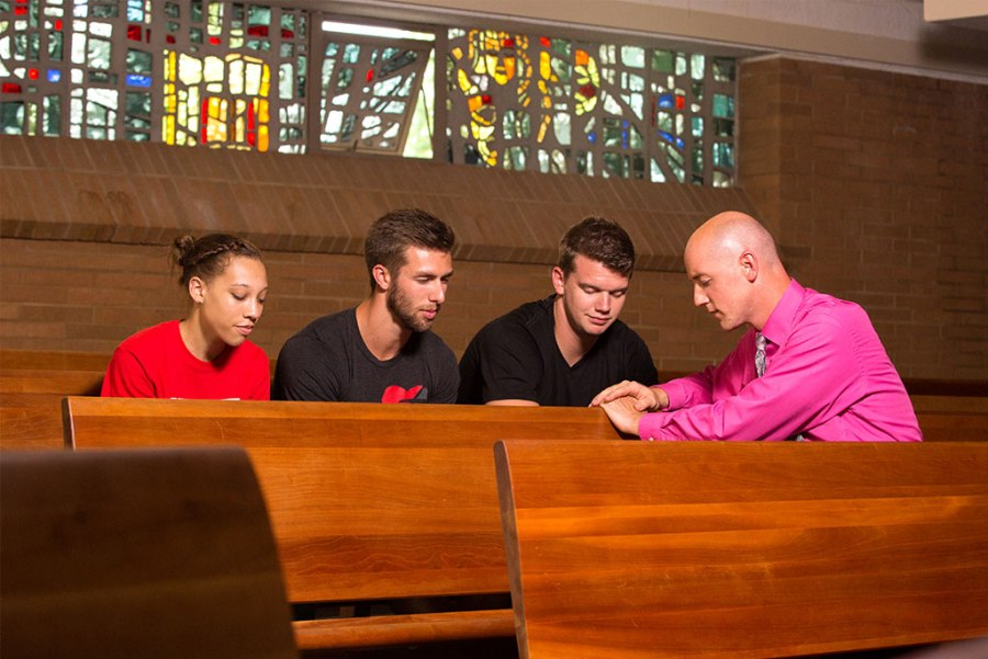 Concordia University Ann Arbor, Mich., Campus Pastor Rev. Ryan Peterson, right, prays with students in the school's Chapel of the Holy Trinity. Also pictured, from left, are Mikaela Morgan, Logan Taylor and Michael Salminen. Two recent surveys show high levels of student satisfaction and spirituality at the school, part of the LCMS Concordia University System. (Courtesy of Concordia University, Ann Arbor)