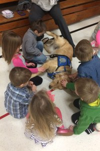 "Preschoolers gather around ""Lizzie,"" a K-9 Comfort Dog (in training) from Lutheran Church Charities, after an April 3 worship service at Martin Luther High School in Northrop, Minn. The service was the first for members of St. James Evangelical Lutheran Church, Northrop, since a March 30 fire destroyed the church building. (Lutheran Church Charities)"