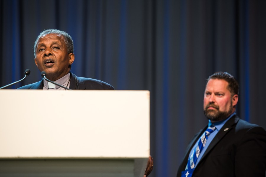 The Rev. Dr. Berhanu Ofgaa, general secretary of the Ethiopian Evangelical Church Mekane Yesus, thanks God for and encourages the two LCMS seminaries on Wednesday, July 13, 2016, at the LCMS convention in Milwaukee. The Rev. Dr. Albert B. Collver III, assistant to the LCMS president and director of church relations, introduced Ofgaa. (LCMS/Michael Schuermann)