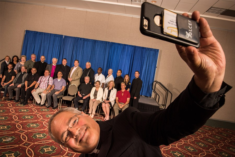 """The Rev. Derek G. Lecakes, president of the LCMS Atlantic District, takes a """"selfie"""" during a group photograph on Wednesday, July 13, 2016, at the 66th Regular Convention of The Lutheran Church—Missouri Synod in Milwaukee. (LCMS/Michael Schuermann)"""