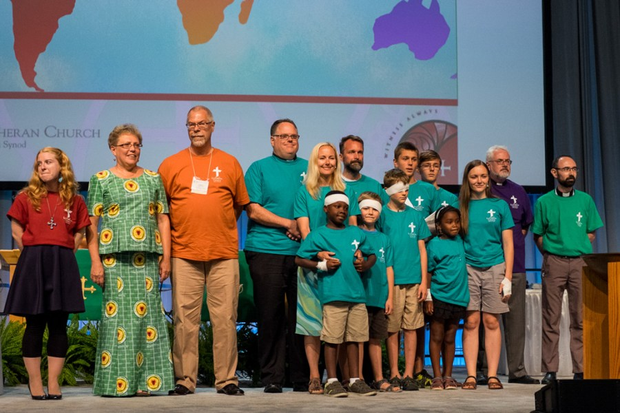 Six career missionaries, with their spouses and families, stand on the convention stage for a special recognition of their service on Monday, July 11, in Milwaukee. (LCMS/Michael Schuermann)
